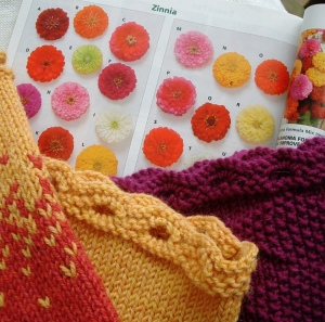 Knitted cowls in Zinnia Cowl pattern against a page of zinnias in a seed catalog
